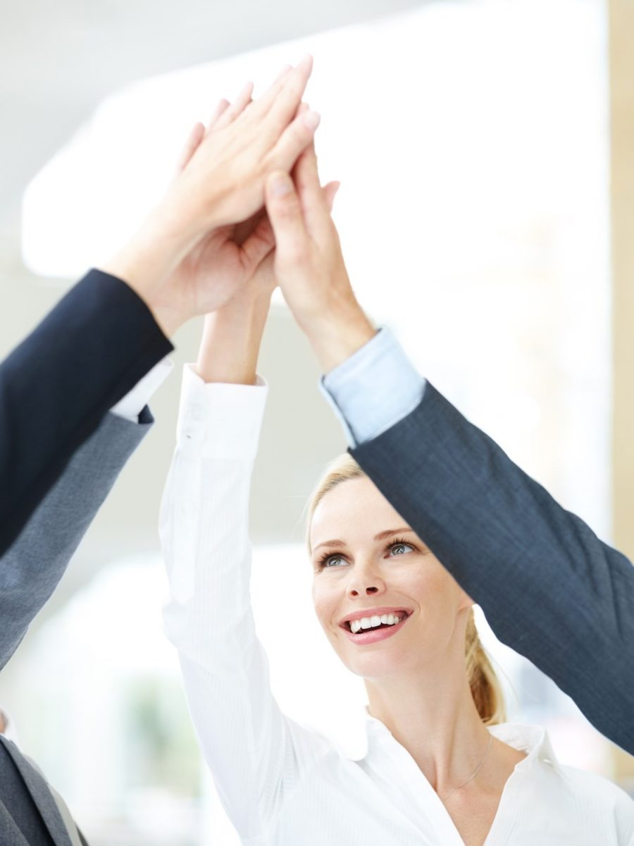 Pretty businesswoman looking up at her hand raised in unity with those of her coworkers - copyspace